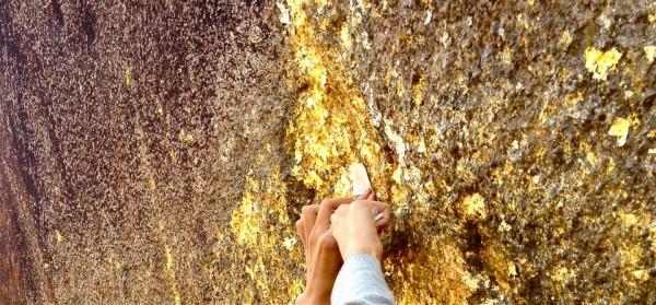 巨大な岩に金箔を貼る手