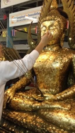 仏像に金箔を貼る手