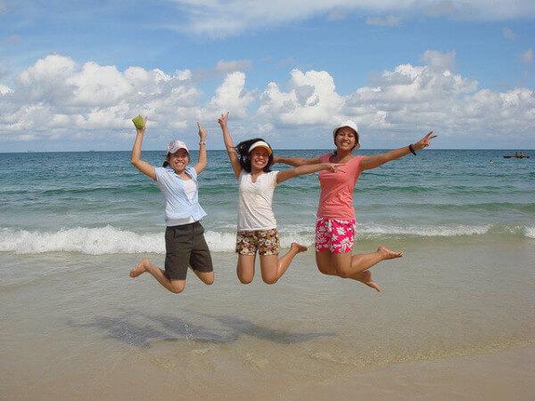 ビーチで跳ねる3人の女性