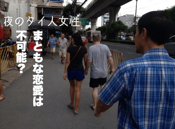手を繋いで歩く夜のタイ人女性と初老の白人男性