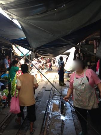 電車通過後にテントを元に戻し始める商人達