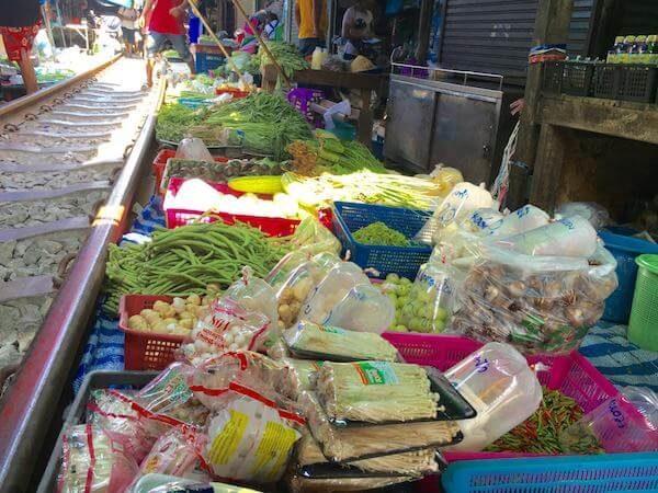 メークロン市場の線路脇で売られている野菜