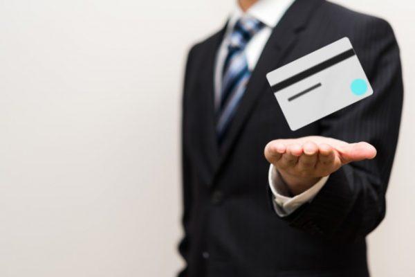 クレジットカードを持つスーツの男性