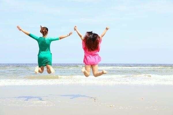 ビーチでジャンプしている二人の女性