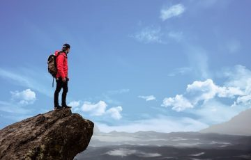 山頂に立つ学生バックパッカー