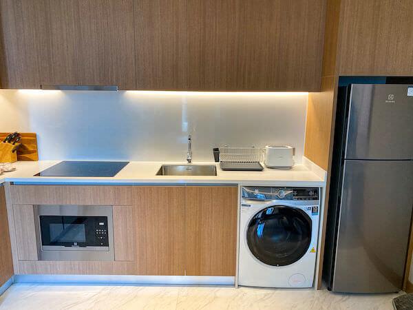 キンプトン マーライ バンコク(Kimpton Maa-Lai Bangkok)の1ベッドルーム レジデンス(One Bed Room Residence)客室に備えられている乾燥機能付き洗濯機と冷蔵庫とキッチン