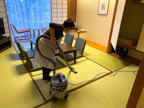 掃除機をかけている客室清掃スタッフ