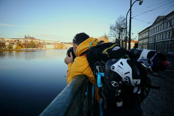 川岸で写真を撮るバックパッカー