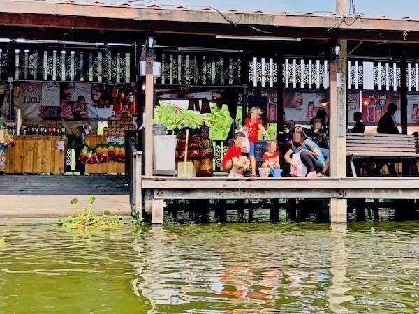 パンブリー水上マーケットでタンブンしているタイ人家族
