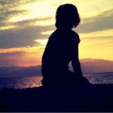 ビーチで夕日を眺めている女性 アイキャッチ画像
