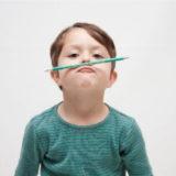 鼻の上に鉛筆を乗せて遊んでいる男の子