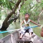 トンレサップ湖でボートを漕ぐ子供のカンボジア人