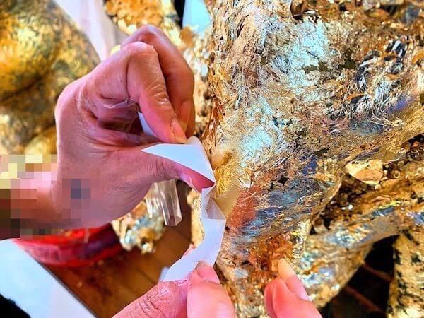 参拝所内のガネーシャ像に金箔を貼る様子2