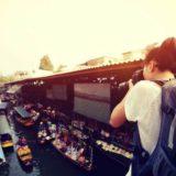 水上マーケットを撮影している女性旅行者