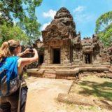 遺跡の写真をスマートフォンで撮る女性旅行者
